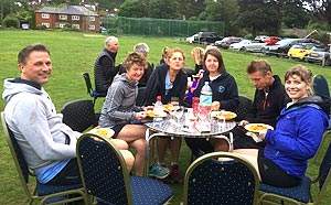 Group sitting around table enjoying their club supper