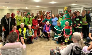 Runners in Xmas fancy dress singing carols to residents in a care home