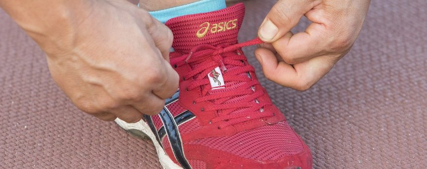 Runner tying laces of running shoe