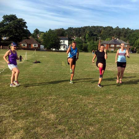 Runners warming up for Covid speed training session at the Bourne Green