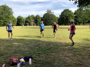 Runners warming up for Covid speed training session in Farnham Park