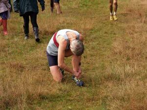 Jane Georghiou tightening shoe laces ready for start of 2014 SXCL race at Farnham