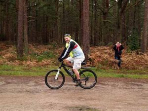Richard Shepherd on bike behind the runners at the 2014 SXCL race at Farnham