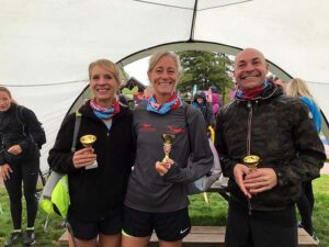 Emma Pearson and Sarah Hill with Philp Barker with trophies at 2018 Alice Holt 10k