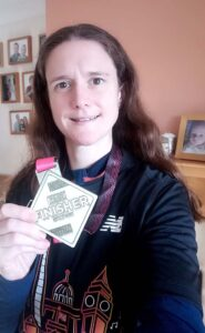 Clair Bailey with medal and T shirt after the 2020 Vitality 10km