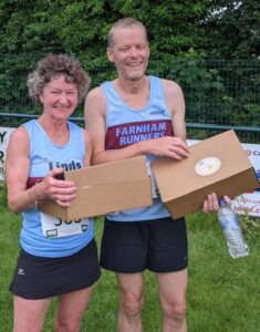 Linda Tylar and Terry Copeland with their 2021 Alresford 10km prizes